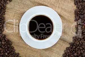 Coffee cup with coffee beans arranged on sack