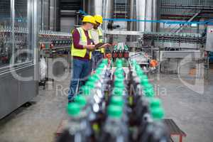 Two factory workers monitoring cold drink bottles on production line
