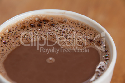 Close-up of white coffee cup with froth