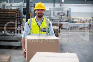 Portrait of factory worker carrying cardboard boxes