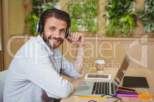 Portrait of male business executive sitting with laptop and listening song