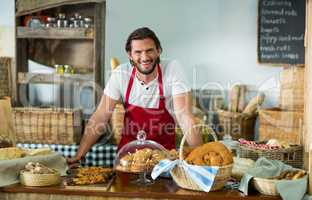 Portrait of male staff standing at counter in bake shop