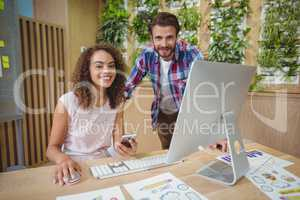 Portrait of executives smiling at desk while working on personal computer