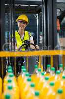 Female factory worker loading packed juice bottles on forklift in factory