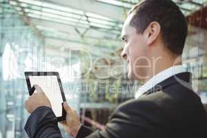 Smiling business executive using digital tablet on platform