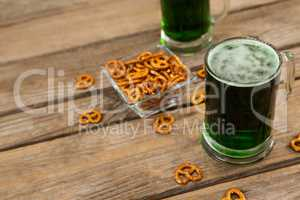 St Patricks Day two mugs of green beer with pretzel