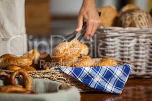 Staff holding bread with tong in bakery shop
