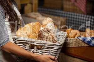 Female staff holding wicker basket of various breads at counter in bakery shop