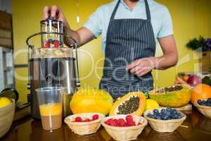 Shop assistant preparing fruit juice