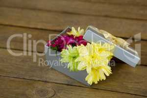 Gift box with flowers on wooden surface