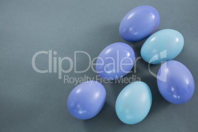 Violet and turquoise Easter eggs on grey background