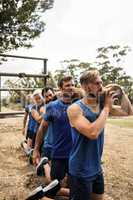 People holding a heavy wooden log during boot camp