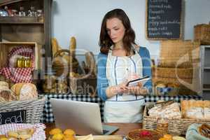 Staff looking at laptop while writing in diary at bakery counter