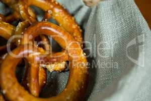 Close-up of pretzel breads in wicker basket at counter