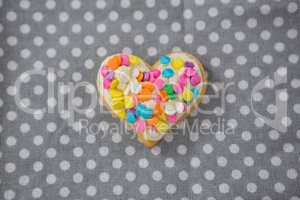 Decorated heart shape cookie against polka dot background