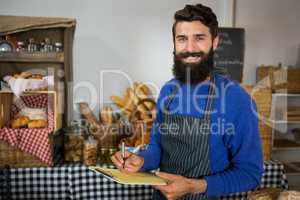 Smiling male staff writing on clipboard at counter in bakery shop