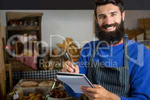 Smiling male staff writing on notepad at counter in bakery shop
