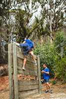 Female trainer assisting man to climb a wooden wall