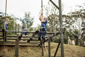 Fit woman climbing down the rope during obstacle course