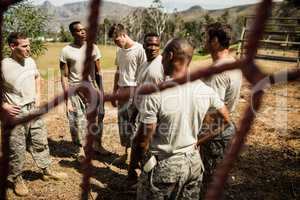 Military soldiers interacting with each other near fitness trial