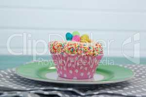 Cupcake with Easter eggs served in plate on a napkin