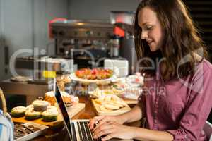 Woman using laptop at bakery counter