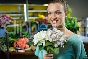 Portrait of woman holding a bunch of flowers
