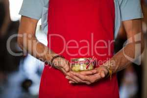 Shop assistant holding a jar of pickle in grocery shop