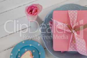 Gift box, flower vase and cookie on wooden surface