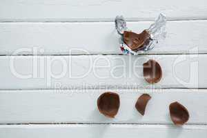 Broken chocolate Easter on wooden surface