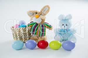Basket with Easter eggs and two toy Easter bunny