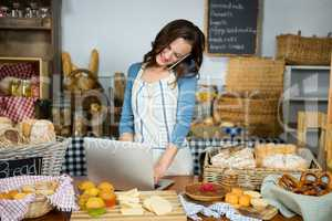 Smiling staff using laptop while talking on mobile phone at bakery counter
