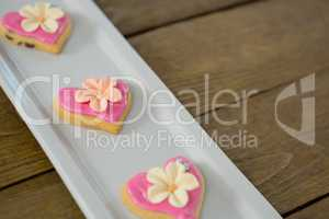 Heart shape cookies in tray on wooden plank