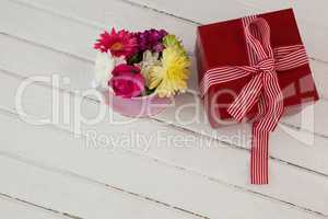 Gift box and fresh flowers on wooden surface