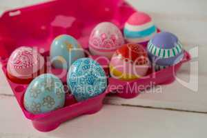 Multicolored Easter eggs in the pink carton