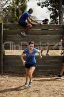Woman running while trainer assisting men to climb a wooden wall