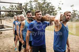 People carrying a heavy wooden log during boot camp