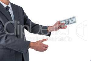 Mid section of businessman holding one hundred dollar