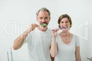 Couple brushing their teeth with toothbrush at home