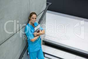 Portrait of female surgeon holding clipboard and digital tablet on staircase