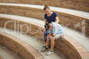 Schoolgirl consoling her sad friend on steps in campus