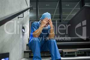 Tensed male surgeon sitting with hands on forehead on staircase