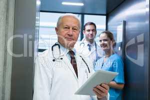 Portrait of doctors and surgeon standing in elevator