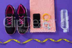 Sneakers, water bottle, towel, measuring tape mobile phone with headphones and fitness band