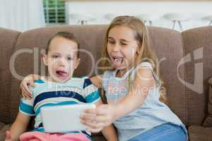 Sister and brother making funny faces while taking selfie from mobile phone