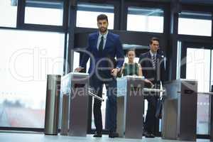 Businessman passing through turnstile gate