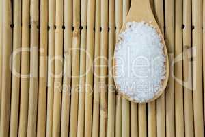Salt in wooden scoop kept on bamboo mat