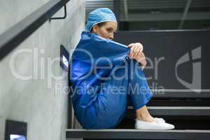 Thoughtful female surgeon sitting on staircase