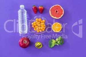 Water bottle, measuring tape, various fruits, vegetable and diet breakfast