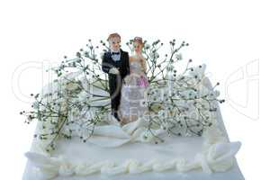 Wedding cake with couple figurines and flowers